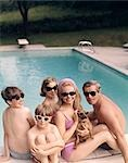 1960s 1970s FAMILY ALL WEARING SUNGLASSES BESIDE SWIMMING POOL