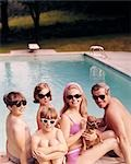 1960s FUNNY FAMILY FATHER MOTHER SONS DAUGHTER WITH DACHSHUND DOG WEARING SUNGLASSES SITTING TOGETHER BY SWIMMING POOL