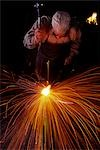 BLACKSMITH WORKING WHITE HOT IRON WITH A HAMMER RED AND ORANGE SPARKS FLYING IN ALL DIRECTIONS Stock Photo - Premium Rights-Managed, Artist: ClassicStock, Code: 846-03165887