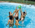 1970s GROUP TEENS BOYS GIRLS IN POOL JUMPING AFTER BALL POOL PARTY