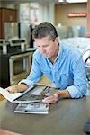 Man in Appliance Store Reading Brochures Stock Photo - Premium Rights-Managed, Artist: Ron Fehling, Code: 700-03178529