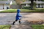Boy Walking through Puddles on Street
