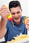 Man squeezing mustard on fries Stock Photo - Premium Rights-Managed, Artist: Glowimages, Code: 837-03182802