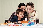 Boy and a girl blowing out birthday candles with their father Stock Photo - Premium Rights-Managed, Artist: Glowimages, Code: 837-03183337