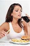 Woman drinking a cola with hamburger and fries Stock Photo - Premium Rights-Managed, Artist: Glowimages, Code: 837-03183663