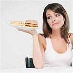 Woman holding a hamburger in one hand and frowning Stock Photo - Premium Rights-Managed, Artist: Glowimages, Code: 837-03184065