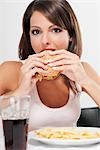 Portrait of a woman eating a burger Stock Photo - Premium Rights-Managed, Artist: Glowimages, Code: 837-03184353