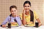 Portrait of a mother and daughter with burgers and fries Stock Photo - Premium Rights-Managed, Artist: Glowimages, Code: 837-03184473