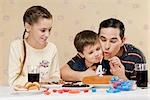 Man blowing out birthday candle with his son and daughter Stock Photo - Premium Rights-Managed, Artist: Glowimages, Code: 837-03184515