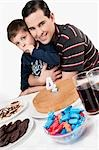 Portrait of a man and his son with a birthday cake in front of them Stock Photo - Premium Rights-Managed, Artist: Glowimages, Code: 837-03184549
