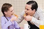Close-up of man and his daughter eating croissants Stock Photo - Premium Rights-Managed, Artist: Glowimages, Code: 837-03184615