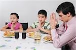 Family praying before lunch Stock Photo - Premium Rights-Managed, Artist: Glowimages, Code: 837-03184663