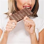 Woman eating a bar of chocolate Stock Photo - Premium Rights-Managed, Artist: Glowimages, Code: 837-03184741