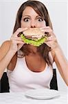 Woman eating a hamburger Stock Photo - Premium Rights-Managed, Artist: Glowimages, Code: 837-03185826