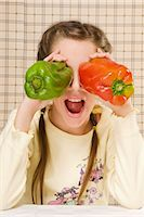Close-up of a girl holding bell peppers over her eyes Stock Photo - Premium Rights-Managednull, Code: 837-03187391