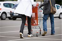 person walking on parking lot - Shoppers pushing shopping cart in parking lot Stock Photo - Premium Royalty-Freenull, Code: 632-03193717
