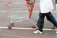 empty shopping cart - Empty shopping cart being pushed across parking lot Stock Photo - Premium Royalty-Freenull, Code: 632-03193742