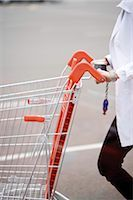 empty shopping cart - Shopping cart being pushed across parking lot Stock Photo - Premium Royalty-Freenull, Code: 632-03193751