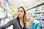 Woman selecting bottle of detergent from supermarket shelf Stock Photo - Premium Royalty-Freenull, Code: 632-03193760