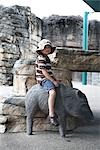 Boy Sitting on Statue of Boar Stock Photo - Premium Royalty-Free, Artist: Mark Peter Drolet, Code: 600-03195017