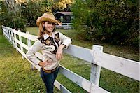 Portrait of young cowgirl standing next to fence on farm Stock Photo - Premium Rights-Managednull, Code: 842-03198553