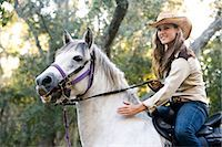 Portrait of young cowgirl riding white Gelding horse Stock Photo - Premium Rights-Managednull, Code: 842-03198564