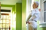 Senior woman leaning against wall in hallway of house Stock Photo - Premium Rights-Managed, Artist: Kablonk! RM, Code: 842-03199405