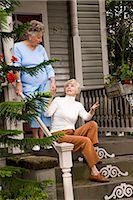 Elderly woman and adult daughter on front porch of hous