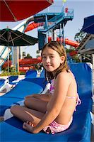 Young girl in swimsuit sitting on deck chair at water park Stock Photo - Premium Rights-Managednull, Code: 842-03200277