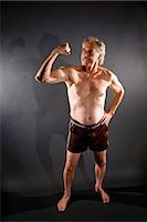Senior man flexing muscles against gray background Stock Photo - Premium Rights-Managednull, Code: 842-03200643