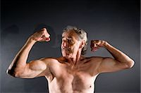 Senior man flexing muscles against gray background Stock Photo - Premium Rights-Managednull, Code: 842-03200645