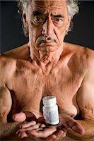 shirtless men - Old man holding medicine bottle, studio shot Stock Photo -