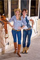 Teenage girl and mother in stable with saddle Stock Photo - Premium Rights-Managednull, Code: 842-03200693