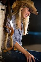 Teenage girl wearing straw cowboy hat sitting in stable Stock Photo - Premium Rights-Managednull, Code: 842-03200728
