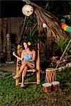 Young Hispanic woman sitting in chair with maracas and bongo drums on tropical island Stock Photo - Premium Rights-Managed, Artist: Kablonk! RM, Code: 842-03200818