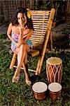 Young Hispanic woman sitting in chair next to bongo drums on tropical island Stock Photo - Premium Rights-Managed, Artist: Kablonk! RM, Code: 842-03200821