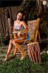 Young Hispanic woman sitting in chair playing bongo drums on tropical island Stock Photo - Premium Rights-Managed, Artist: Kablonk! RM, Code: 842-03200823
