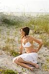 Young woman in white bikini top and skirt sitting on sand dunes of beach Stock Photo - Premium Rights-Managed, Artist: Kablonk! RM, Code: 842-03201043