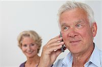 Senior man on the phone with woman in background Stock Photo - Premium Royalty-Freenull, Code: 628-03201192