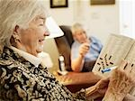 Elderly Couple in Retirement Home, Woman Working on Crossword Puzzle Stock Photo - Premium Royalty-Free, Artist: Matthew Plexman, Code: 600-03210389