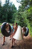 Teenagers Carrying Inner Tubes and a Canoe to the Lake, Near Portland, Oregon, USA Stock Photo - Premium Royalty-Freenull, Code: 600-03210542
