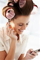 Woman in curlers talking on cell phone Stock Photo - Premium Royalty-Freenull, Code: 635-03229136