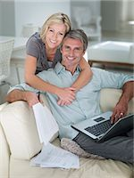 Couple using laptop in living room Stock Photo - Premium Royalty-Freenull, Code: 635-032291