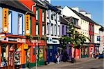 Kenmare, Co Kerry, Ireland; Traditional signs hanging from shopfronts