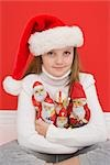 Portrait of Girl Holding Santa Ornaments Wearing Santa Hat Stock Photo - Premium Royalty-Free, Artist: Ursula Klawitter, Code: 600-03240863