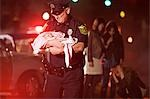 Police officer rescuing a baby Stock Photo - Premium Royalty-Freenull, Code: 614-03241400