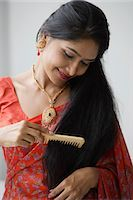 singapore traditional costume lady - Indian woman wearing a sari and combing her hair Stock Photo - Premium Royalty-Freenull, Code: 655-03241651
