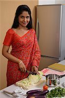 singapore traditional costume lady - Indian woman wearing a sari while making dinner in the kitchen Stock Photo - Premium Royalty-Freenull, Code: 655-03241687