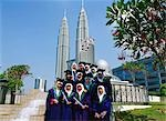 University graduates taking photos in the park with Patrons Towers at background, Kuala Lumpur, Malaysia