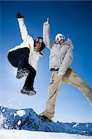 Two friends jumping outside in the snow Stock Photo - Premium Royalty-Freenull, Code: 640-03256121